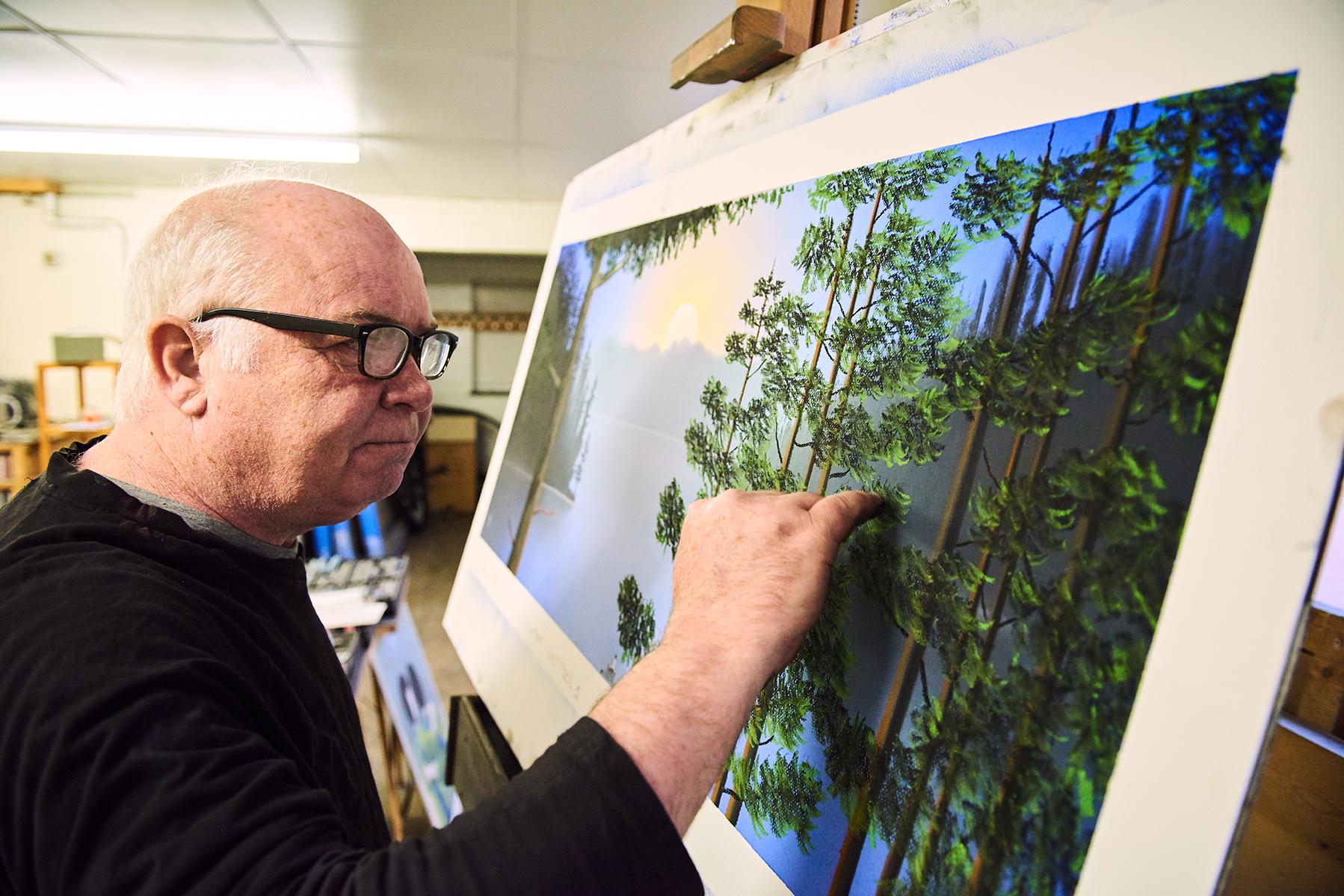 Artist Mackenzie Thorpe working on landscape painting close up