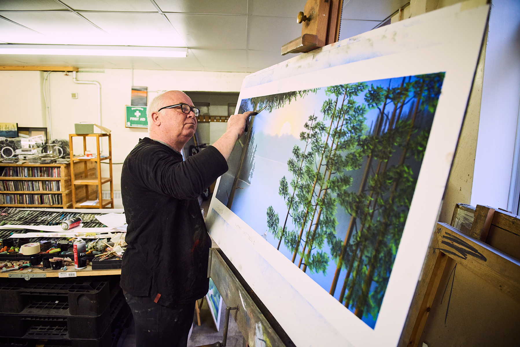 Artist Mackenzie Thorpe working on landscape painting